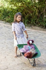 Cute girl pushing a wheelbarrow filled with toys