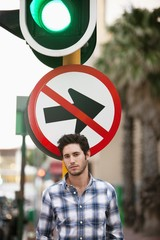 "Man with ""No Entry"" sign and traffic light in the background"