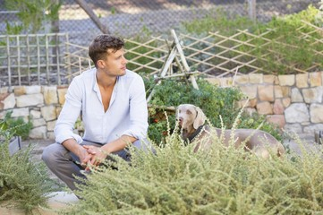 Contemplative man with a dog in garden