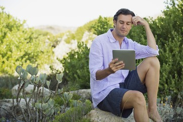 Mid adult man sitting on a rock and using a digital tablet
