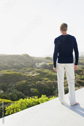 Rear view of a young man looking at view from the terrace of a house