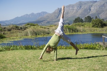 Cute little boy doing cartwheel against mountain