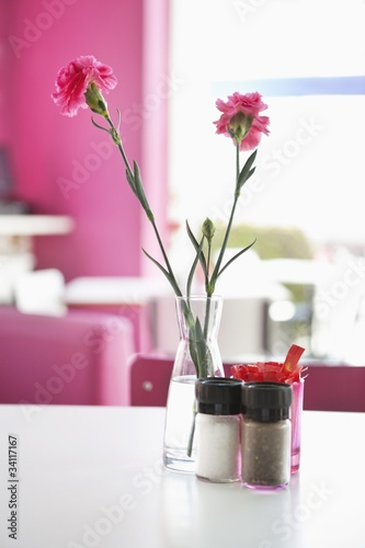 Vase with pink flowers and salt and pepper shakers on a table in a restaurant