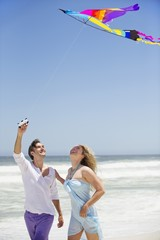 Mid adult couple flying kite on the beach