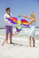 Mid adult couple holding animal shaped kite on the beach