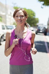 Beautiful young woman listening to mp3 player while jogging