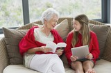 Senior woman and her granddaughter looking at each other and smiling