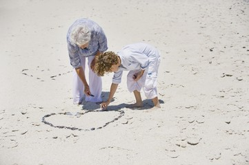 Senior woman and her grandson making a heart shape on the beach