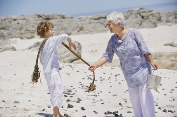 Senior woman with her grandson collecting shell on the beach