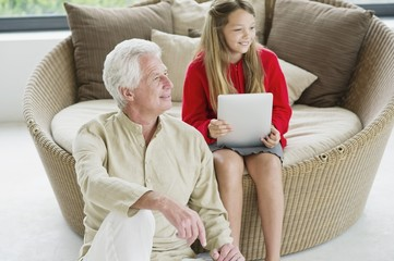 Senior man sitting with his granddaughter holding a digital tablet