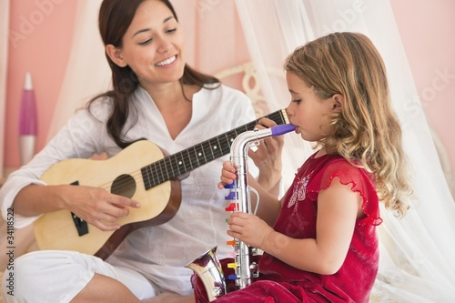 Woman playing guitar with her daughter playing saxophone