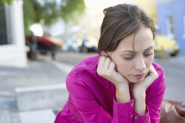 Depressed young woman sitting at the roadside