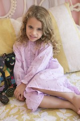 Portrait of a little girl sitting on the bed