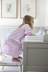 Cute little girl bending over bathroom sink