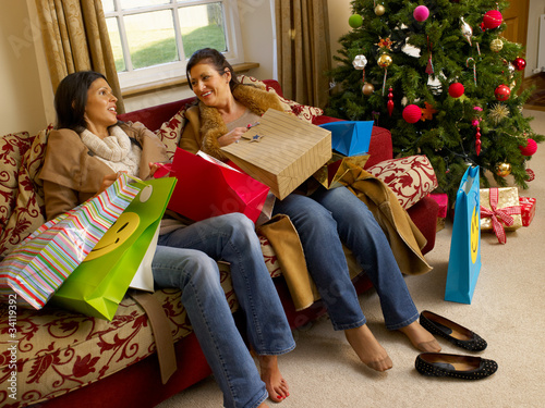 Hispanic mother and daughter resting after Christmas shopping