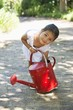 Cute little girl picking up a watering can