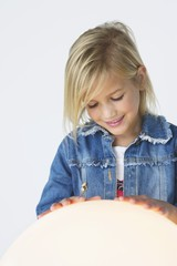 Smiling girl touching an illuminated sphere