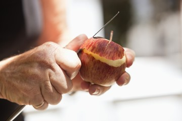 Close-up of man's hand peeling an apple