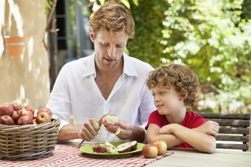 Father peeling apple with son