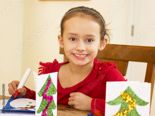 Young mixed race child making Christmas cards