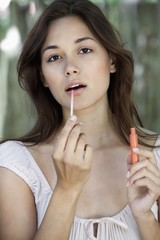 Portrait of a beautiful young woman applying lip gloss