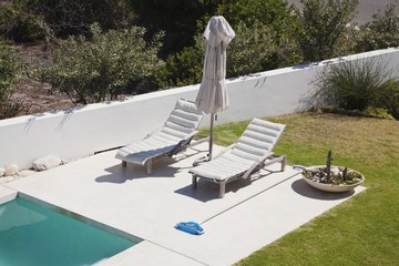 High angle view of lounge chairs at poolside
