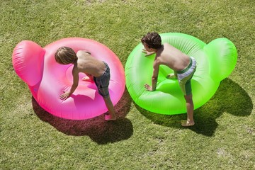 Two boys playing with inflatable rings