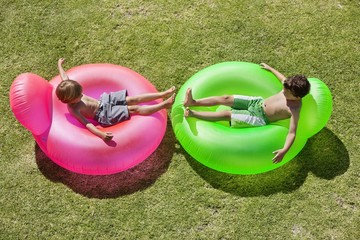 Two boys relaxing on inflatable rings