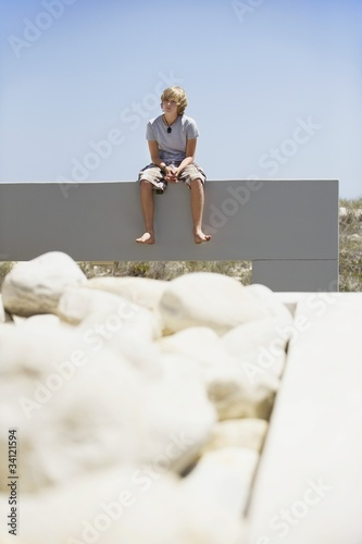 Teenage boy sitting at the edge of a terrace