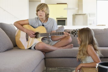 Girl looking at a her brother playing a guitar