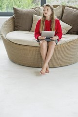 Girl sitting in a wicker couch using a digital tablet