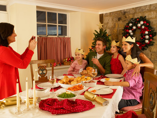 Hispanic family taking photos of Christmas dinner