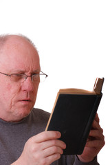 Older Balding Man in gray Shirt Reading a Black Book or bible