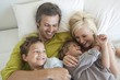 Couple with their children relaxing in bed