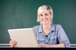 lachende junge frau mit laptop vor einer tafel