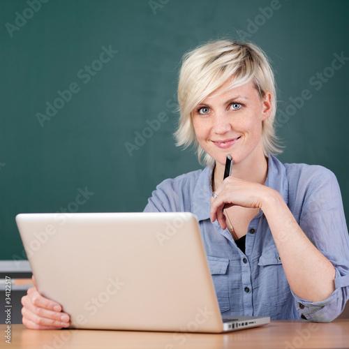 lächelnde junge frau lernt am laptop