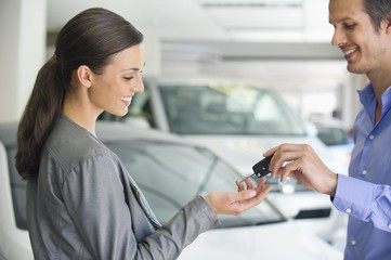 Happy salesperson handing woman car key in showroom