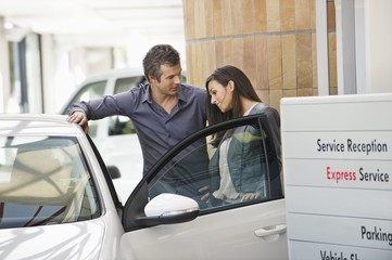 Couple looking inside car at showroom