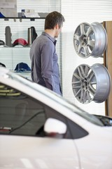 Mid adult man looking at hubcap in car showroom