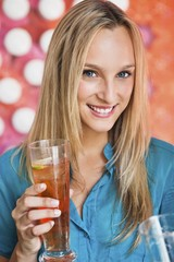 Portrait of a beautiful woman having ice tea in a bar and smiling
