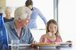 Girl eating food at a dining table with her grandfather sitting near her