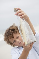 Boy looking at message in a bottle on beach