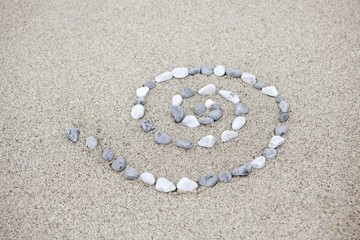 Pebbles arranged in spiral shape on beach