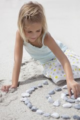 Girl playing with pebbles on beach
