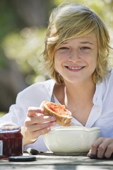 Portrait of a little boy eating bread with jam outdoors