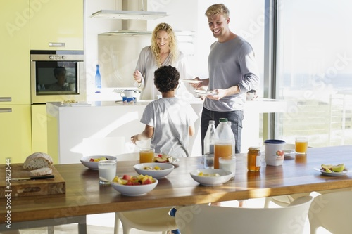 Couple with their son preparing food in a domestic kitchen