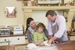 Cute little boy and his parents kneading dough at kitchen