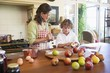 Grandmother and little boy peeling an apple at home