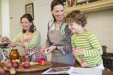 Multi generation family cooking food together at kitchen