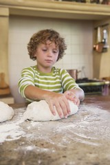 Cute little boy kneading dough at kitchen